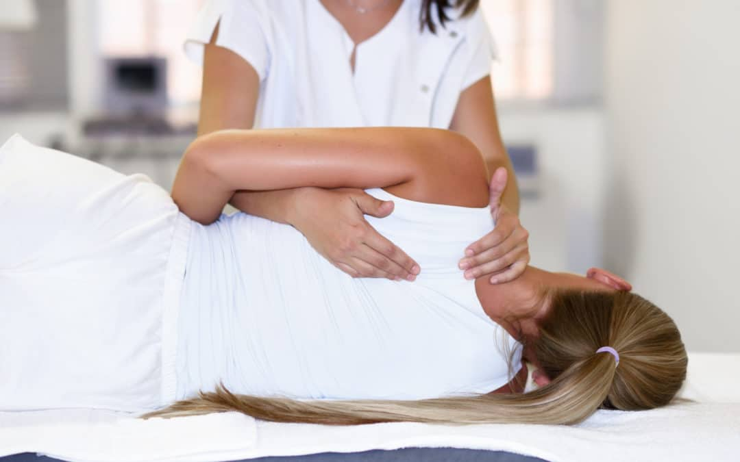 Professional female physiotherapist giving shoulder massage