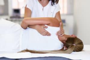 Professional female physiotherapist giving shoulder massage